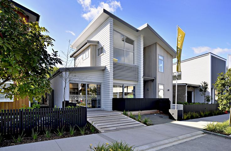 This modern townhouse features an angled roof and a combination of natural and white-painted weatherboards (ID 1276)