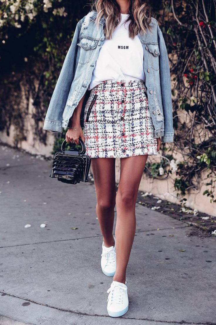A modern interpretation of a classic from the 90s: plaid skirt, sneakers, denim jacket and