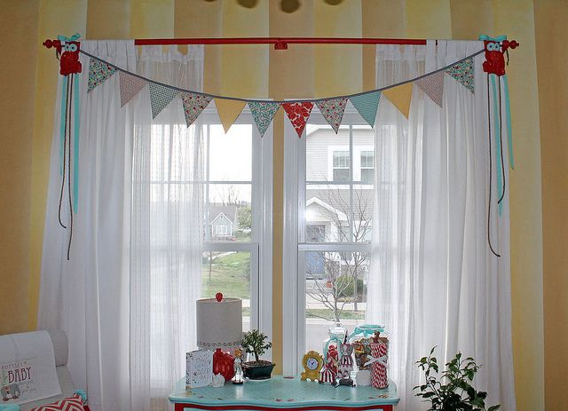 Vintage circus nursery window treatment:  white sheers with pennant banner.  Perfect, simple and inexpensive..