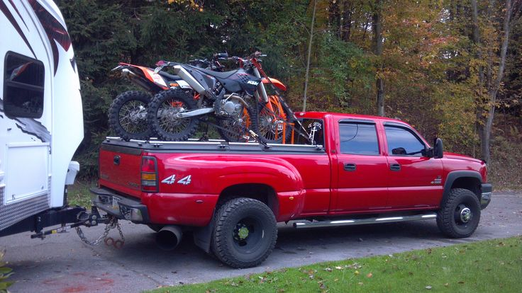 Dirt Bikes on Black Heavy-Duty Truck Bed Cover on Pickup Pulling Trailer | by DiamondBack Truck Covers