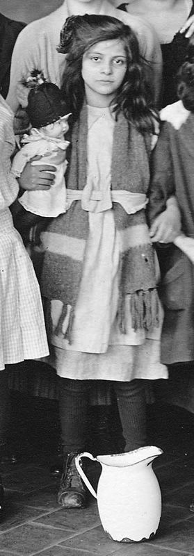 Immigrant at Ellis Island. New York, 1908. In all the uncertainty she has a home grown doll to give comfort.
