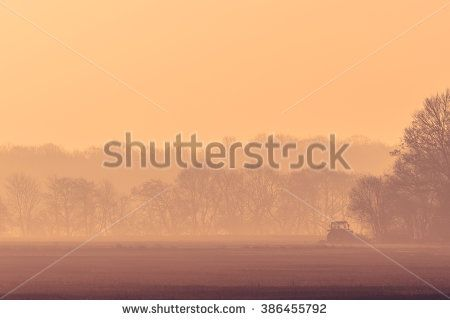 Misty morning with a tractor on a field in the sunrise