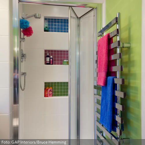Drei kleine Wandnischen, die zur Duschablage dienen, sind mit Fliesen in jeweils Blau, Pink und Grün gestaltet. Die grüne Wandfarbe und die bunten Handtücher nehmen die Töne der bunten Mosaikfliesen wieder auf – so wirkt es schön harmonisch.