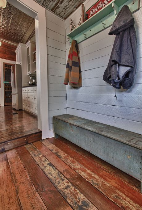 mudroom with reclaimed wood floors, painted plank walls, & antique touches