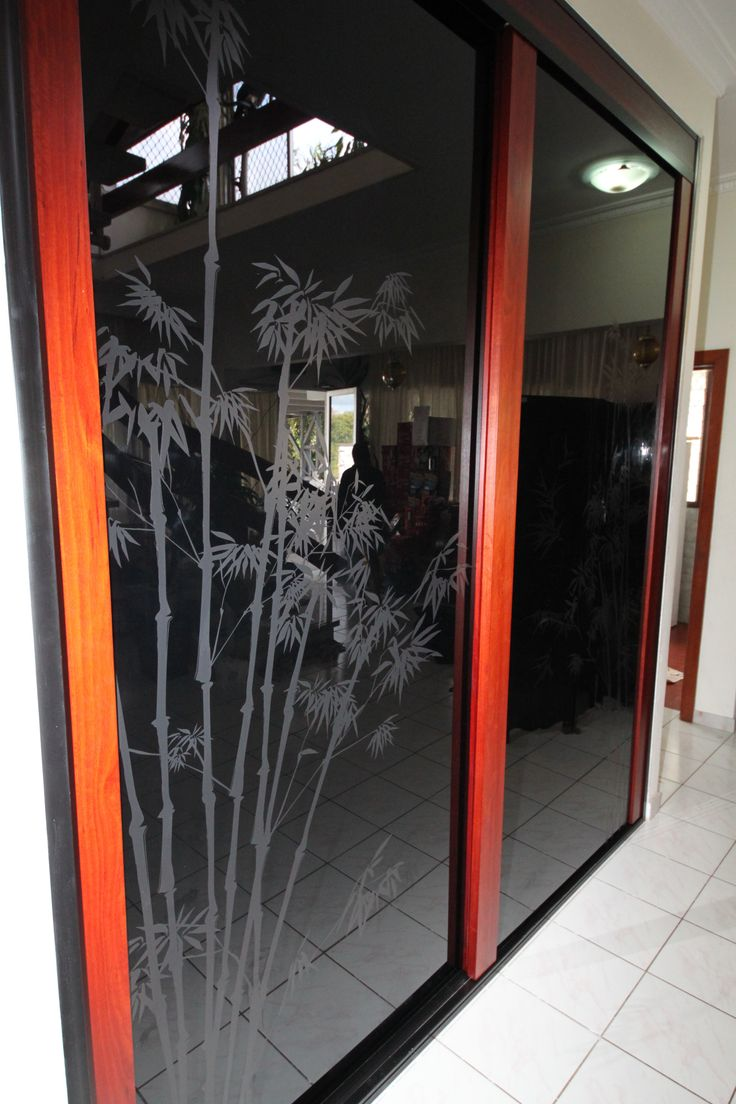Our Infinity Sliding Door offers elegance and charm.   To reflect their personality and style our homeowners elected for a bamboo motif to be printed on the black glass.  www.formfunctionnt.com.au