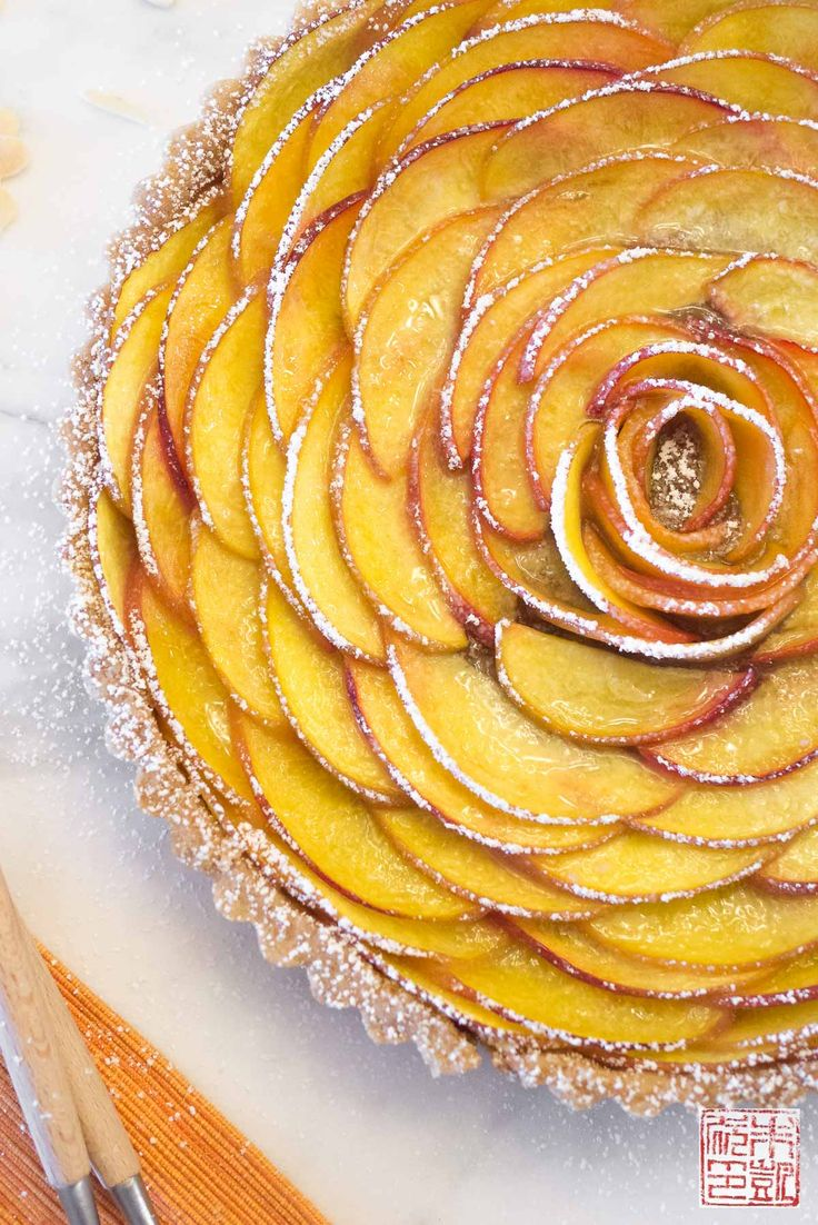 Peach rose tart recipe. Fresh summer peaches arranged in a floral design in an almond tart shell.