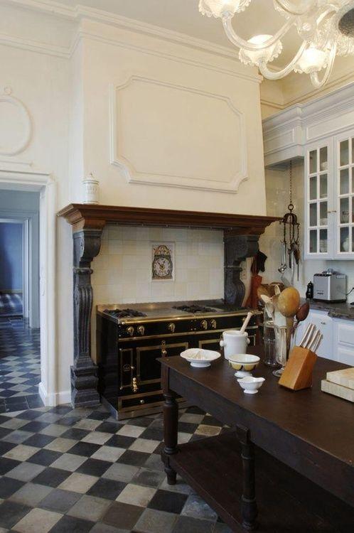Checked floor, black and brass La Cornue range, large island, Murano glass chandelier