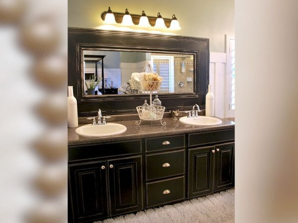 love the black distressed cabinets and the use of chunky molding around the mirror you could frame a large mirror in a track home this way and change the
