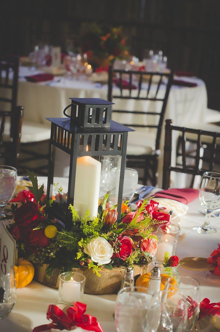 A beautiful fall wedding reception centerpiece featuring #lanterns and #candles Photo by Banana Bugz Photography. #weddingdecor #weddingbouquets #weddingflowers #flowers #fallwedding #gardenwedding #rusticweddings #pumpkins #centerpieces #rustic