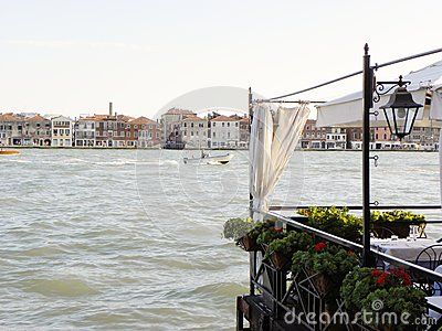 A romantic view on the Giudecca Canal, photo took from a flowery side of a restaurant on the sidewalk, Venice, Italy, Europe