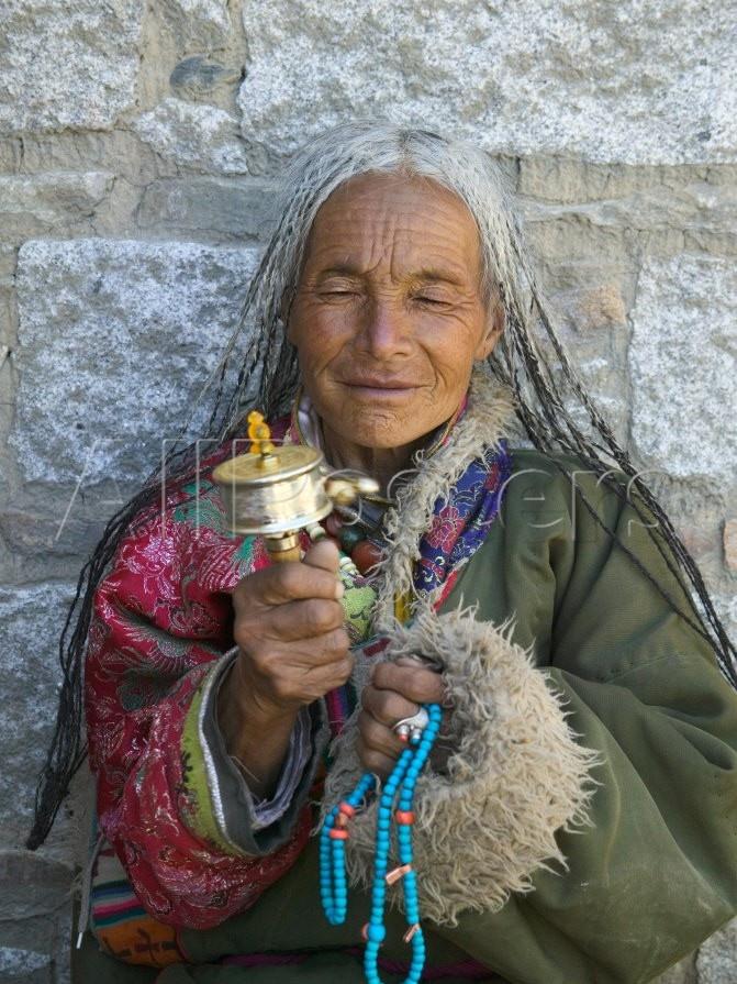 Tibetan Woman Holding Praying Wheel in Sakya Monastery, Tibet, China Photographie par Keren Su