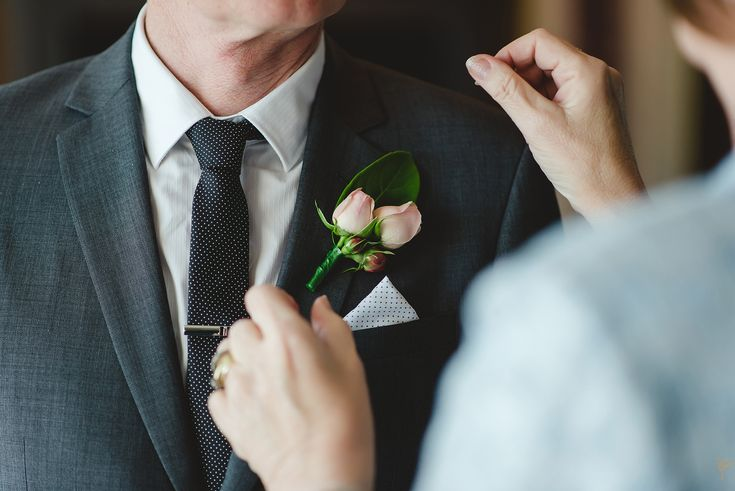 Pale pink button hole on grey suit and charcoal tie.