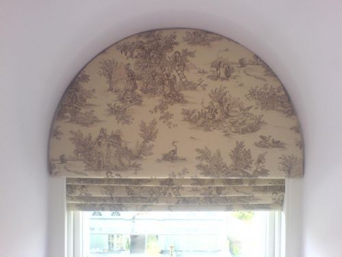 Arched upholstered pelmet over roman blind.