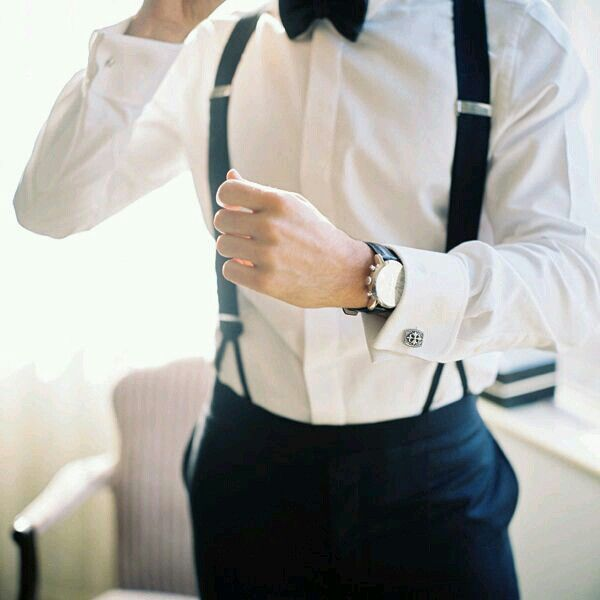 Groom with black suspenders , black pants, white t-shirt and probarly black shoes.