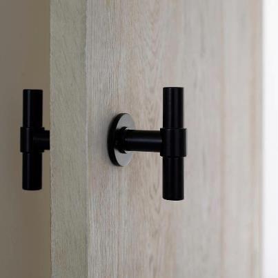 beautiful black door handle on a stunning pale wood door