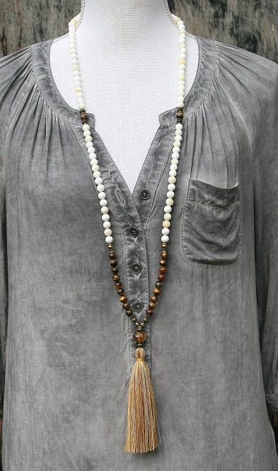 Mala necklace made ​​of 8 mm - 0.315 inch shell and tiger eye gemstones. Together they count as 108 beads. The mala is decorated with hematite and the guru bead is a faceted quartz stone.  The total length of the mala is approximately 100 cm - 39.37 inch.