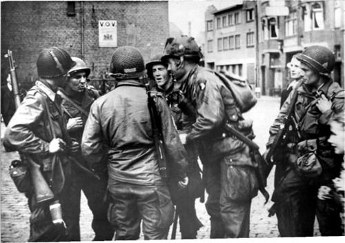 daily dose of Easy Company boys, in Eindhoven, 18 September 1944. From left to right: Amos Taylor, McLauren, Jim Alley, Bill Kiehn (who would later be KIA in Alsace), and Campbell T. Smith. Of course the NCO with his back to the camera is none other than Sgt. Carwood Lipton.