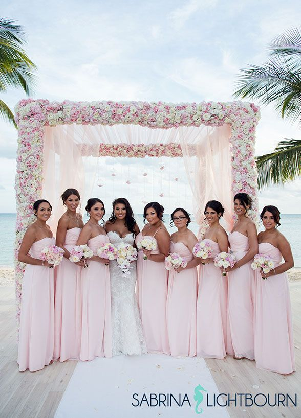 Bridesmaids gather around the bride wearing matching light pink gowns. #BeachWedding #PinkWedding