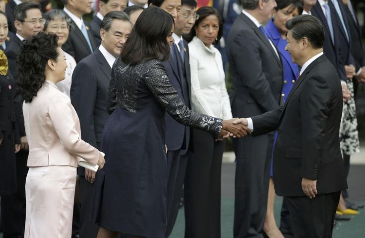 China's first lady Madame Peng Liyuan watches as U.S. first lady Michelle Obama shakes hands with China's President Xi Jinping at the White House in Washington