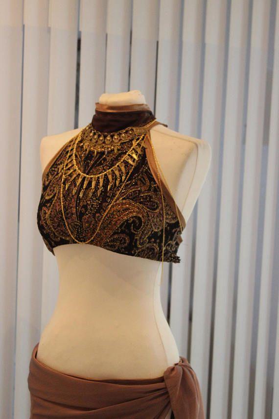 Dieses Tribal Fuson Belly dance Kostüm ist ein absoluter Hingucker. Der Stoff schimmert golden je nach Lichteinfall. Seitlich ist der Rock zum schnüren ebenfalls befindet sich am Oberteil eine Schnürung und Bänder zum individuellen verstellen. Zum Kostüm gehört eine Body Chain und