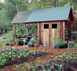 This potting shed features enclosed storage for tools, wheelbarrows, and power equipment. A potting bench and staging area are located beneath an attached shelter, part of which is covered in lattice. The lattice offers partial shade for acclimating plants started indoors or in a greenhouse.