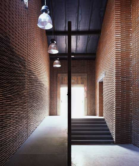 Stacks of reclaimed roof tiles form walls inside this former slaughterhouse in Madrid by Spanish architectArturo Franco.