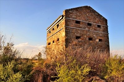 A most unusual feature of this type of blockhouse is a pair of angle bastions at diagonally opposite corners, which were designed to provide for the flanking fire along the walls, similar to the function of Machouli galleries on other patterns, but at ground level. This blockhouse was a two level structure with a lookout tower.Witkop Blockhouse - Boer Wars Memorials and Monuments on Waymarking.com