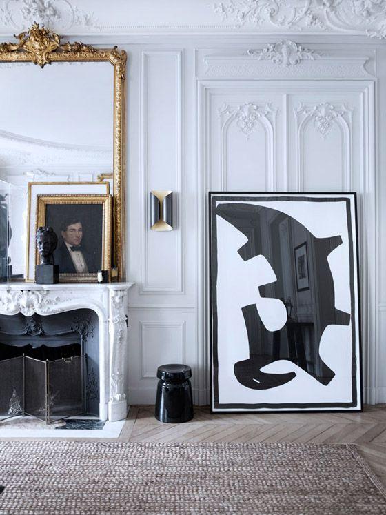 Gilles et Boissier Paris home photo by BW Drejer living room white paneled walls fireplace jute rug gold antiques black white modern art