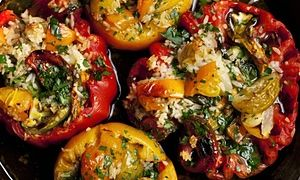 Four beefsteak tomatoes stuffed with orzo and basil in a cast-iron skillet