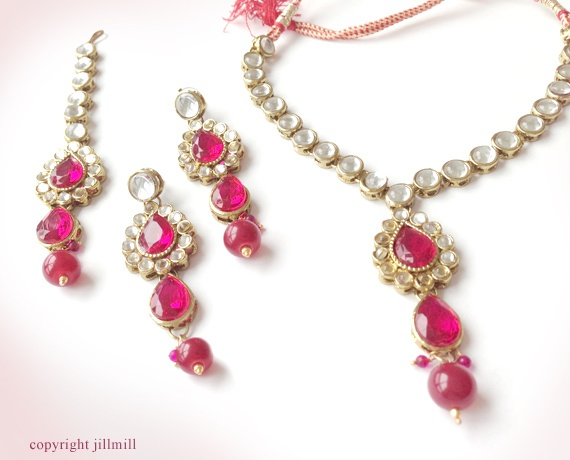 This white kundan with ruby pink stones and beads set showcases an elegant and charismatic look.