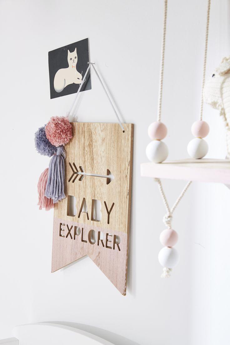 Fanion en bois agrémenté de petits pompons pour décorer la chambre de bébé.