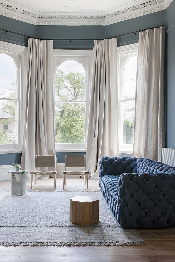 Bay window curtains for living room - An Elegant Living Room With High Ceilings Classic Architectural Details And A Blue Velvet Sofa