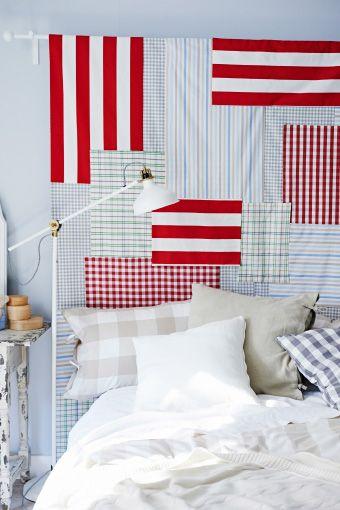 Ein Bett mit RANARP Stand-/Leseleuchte in Elfenbeinweiß und einem selbst gemachten Kopfteil, u. a. mit BERTA RUTA Meterware kariert, mittel/rot.