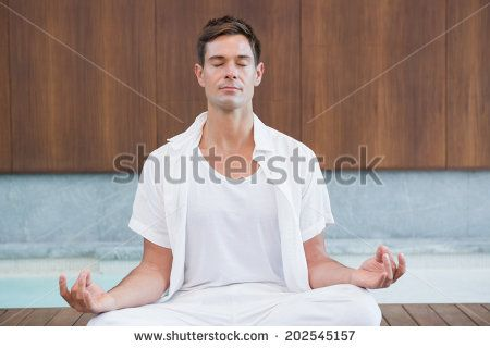 Handsome man in white meditating in lotus pose in health spa
