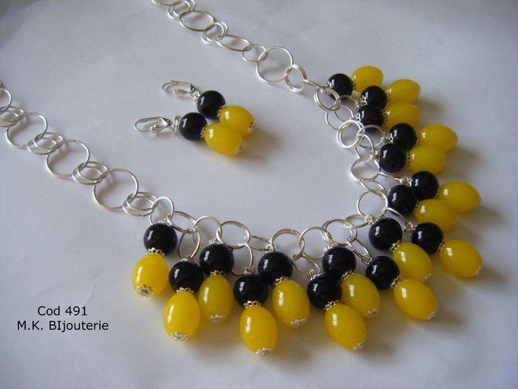 Collar elaborado con huevos de cristal en tono amarillo canario y perla negra, incluye aretes