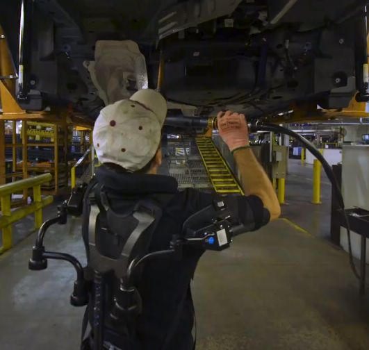 "The EksoVest is designed to reduce worker fatigue and injuries due to overhead assembly tasks. ""Built tough"": That's the slogan used in ads for Ford trucks, which are shown hauling massive loads, t…"