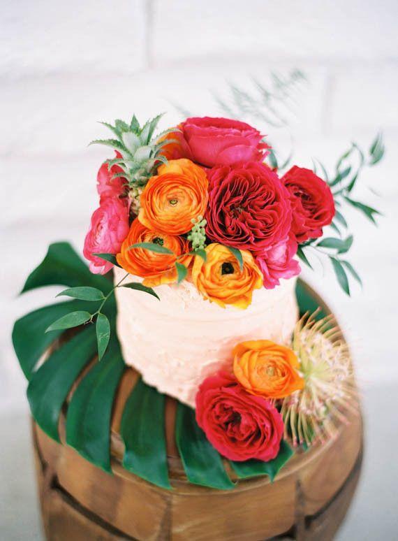 Hochzeitstorte mit bunten Blumen und Palmenblättern