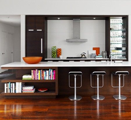 Sleek, Modern Kitchen:  White counter tops and metal bar stools pop against these dark, horizontal-grain wood cabinets.
