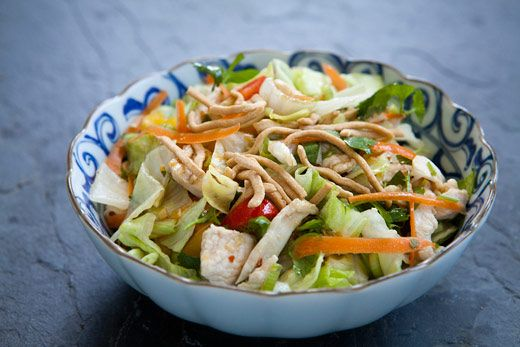 Chinese chicken salad with thinly sliced lettuce, bell peppers, scallions, julienned carrot, cilantro, peanuts, and skinless boneless chicken breast.