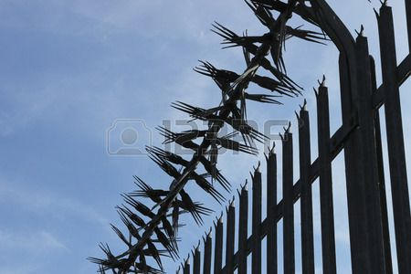 Close up spiky metal fence from a diagonal angle with blue sky background
