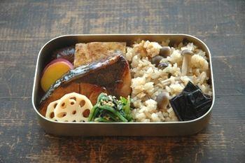 シンプルな昔ながらのお弁当♪炊き込みご飯を半分に、真ん中にぶりの照り焼き、まわりをさつまいもや青菜など色合いも考えられた副菜が囲んでおり、優しい味わいに癒されるランチに。