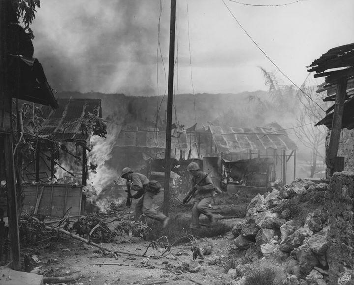 US Marines running through streets of Garapan while engaging in street fighting Saipan Mariana Islands 3 July 1944.