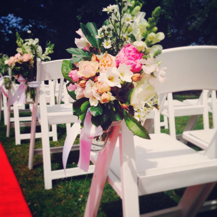 Our first 'Summer' outdoor wedding ceremony at Chateau Yering : our White Americana Folding Chairs have been adorned with Flowers by Helen Dillon
