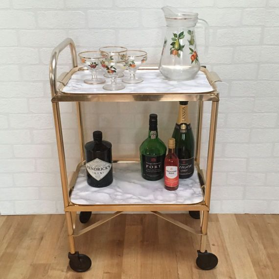 Vintage 1980s small gold drinks trolley with two tier marble effect contact paper removable trays.  A great addition to your evening drinks or your party so you can be the hostess with the mostest!  D E L I V E R Y £40 - Bespoke Courier Company (UK only) FREE - Collection from London, SE21.  C O N D I T I O N We upcycle, restore and update vintage pieces meaning all our furniture has been previously loved. Pieces may show some signs of minor wear and use, which we feel adds to its charm…