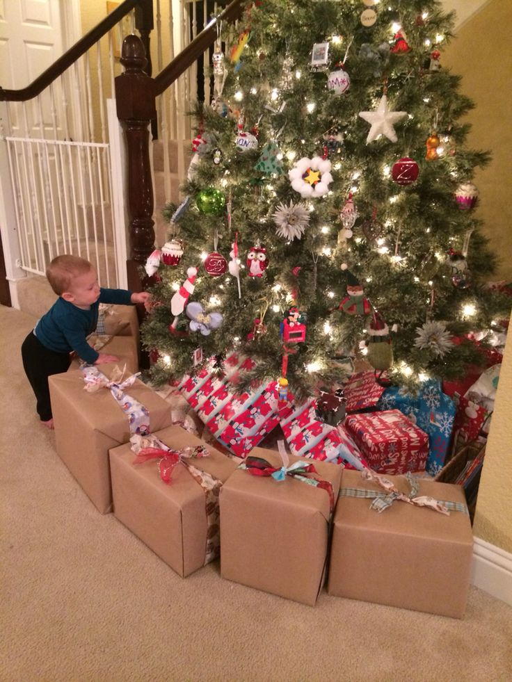 Fake-present barricade (ie...wrapped diaper boxes filled with books) prevents my 9 month old baby from getting under the Christmas tree. I put it far enough out that he can only reach a few baby friendly ornaments.