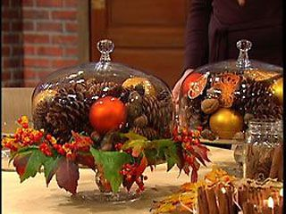 Fall decoration. Pine cones and nuts interspersed with fall colored fruits, balls, etc. in a cloche (a covered cake stand in this case).