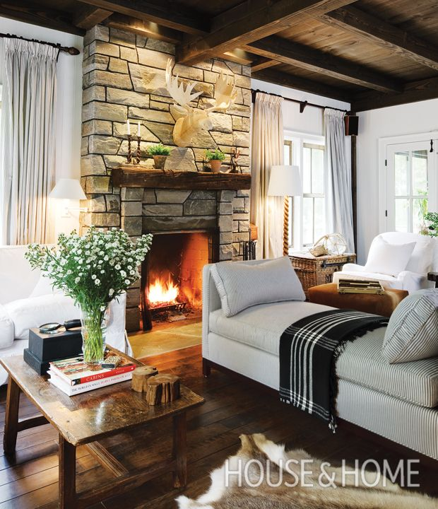 Set in Muskoka, Ontario, this cottage by designer Michael Angus features timbered ceilings, a weighty stone fireplace and plenty of natural accents. | Photographer: Janet Kimber