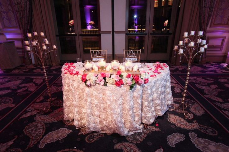 Sweetheart table with a long and low with candles and white hydrenga, hot pink roses, and light pink roses. Candelabras sit on either side of the table. #naakiti