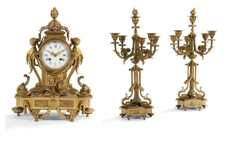 Garniture de cheminée en bronze doré composée d'une pendule à décor de bustes de femme, colombes et carquois, et de deux candélabres à six lumières et montants en console. Le cadran et le mouvement signés… - Ader - 28/10/2015