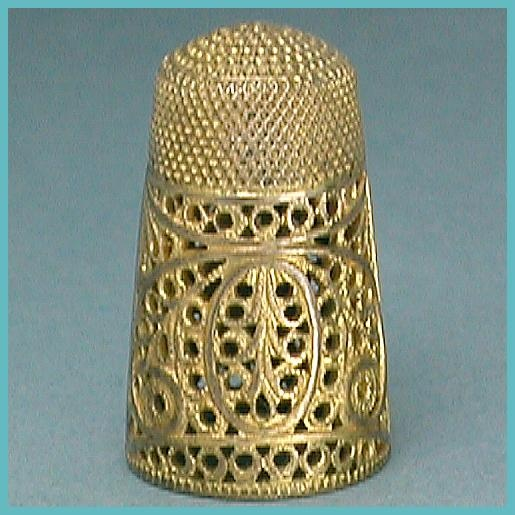 style of the more usual English silver filigree thimbles of the late 18th or early 19th century. This one was cast and pierced to simulate the wirework examples but is made of Pinchbeck or gilded metal/brass. It's a tall thimble (35 mm high) and about an American size 6 (opening is 13.75 mm in diameter).